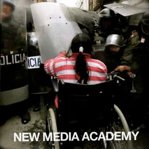 New Media Academy: Man in wheelchair charging a barricade of police in full riot gear