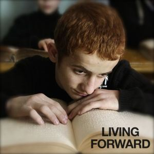 Be Informed_Accessible to All_Living Forward_Blind boy with red hair reading a braille book at school desk